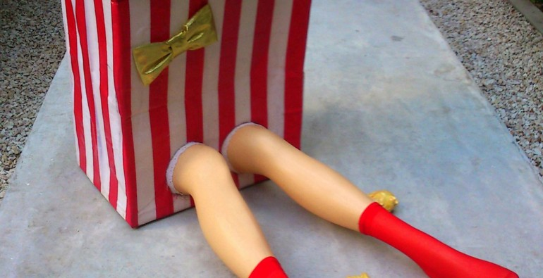 """Miss Popcorn XL"" Giant hyper realistic popcorn bucket with legs wearing red stockings."